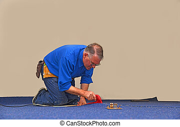 sealing the joint - A floorlayer uses a hot iron to seal the...