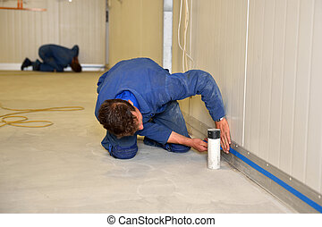 masking the wall - tradesman masks off the height of the...