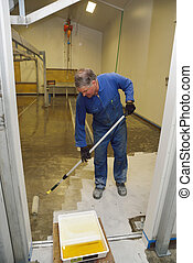 epoxy surface for floor - tradesman applying epoxy product...