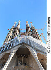 Passion facade at church Sagrada Familia with towers in Barcelona, Spain