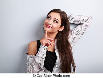 Thinking fun smiling young woman in casual clothing looking up on blue background