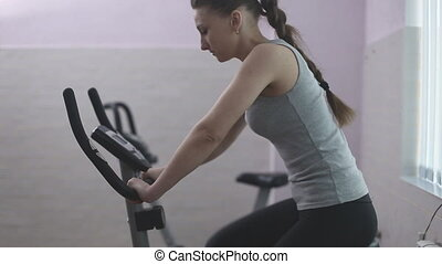 Girl training on a stationary bike in the gym