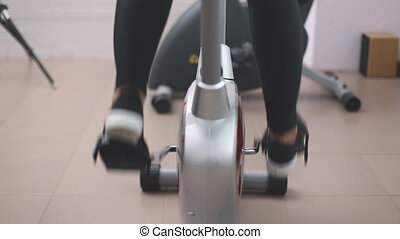 legs twist exercise bike in the gym closeup