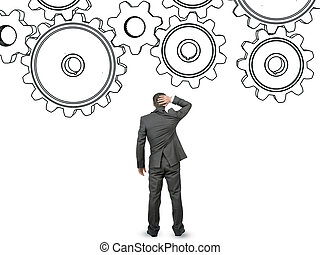 Confused businessman in front of cog wheels isolated on...