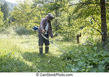 Man wearing protective helmet with goggles while trimming the lawn