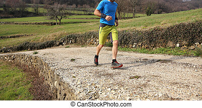 sportsman with running shoes runs during cross country race...