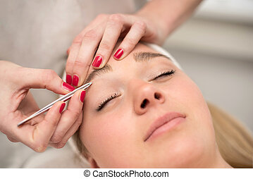 Plucking eyebrows with tweezer by beautician in beauty salon...