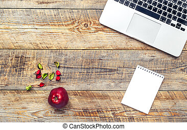 Laptop computer on wooden background with apple fruit.