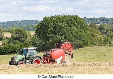 Agricultural baler discharging a round hay bale  in scenic countryside