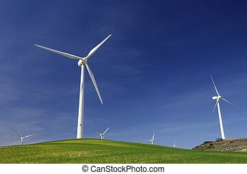 wind energy - windmills on a green hill with blue sky