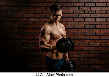 Young sports guy trains the biceps