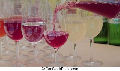 Cranberry juice is poured into glasses.