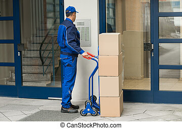 Delivery Man With Trolley Using Security To Enter Building -...