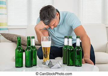 Man Sitting On Sofa In Front Of Beer - Mature Man Sitting On...