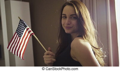 Slow motion footage how young caucasian female is standing in a room and waving an american national flag.