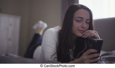 Young attractive brunette lies on a bed and listens to the music on her mobile device, girl moves to the rhythm from melody.
