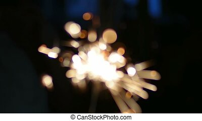 Defocused sparkler in the dark room, toned image