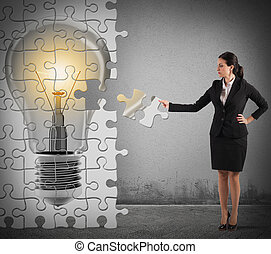 Build an idea puzzle - Woman builds a puzzle with light bulb