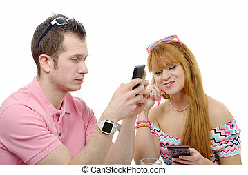 young couple sending text messages on their phones - a young...