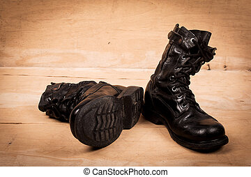 old black combat boots on wooden background