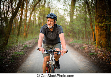 Senior man on his mountain bike outdoors (shallow DOF; color...