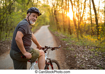 Senior man on his mountain bike outdoors shallow DOF; color...