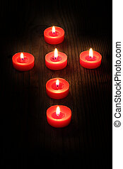 candles in a cross - burning candles arranged in a cross,...