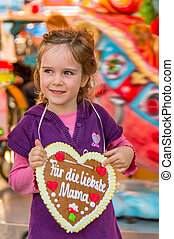 child with gingerbread heart. mother's day - a child holding...