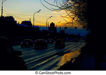 City street and cars on sunset in early spring time