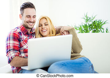Young couple browsing internet at home, using laptop and...