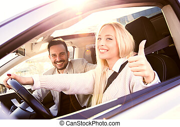 Couple buying a car - Young man and woman smile at the...