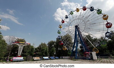 Ferris wheel on a sunny day on blue sky and green forest