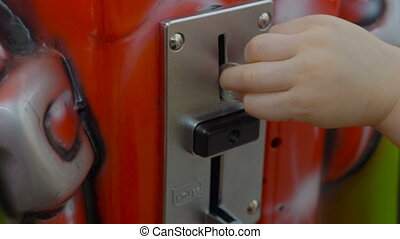 Child's hand throws coin into a slot machine, close up