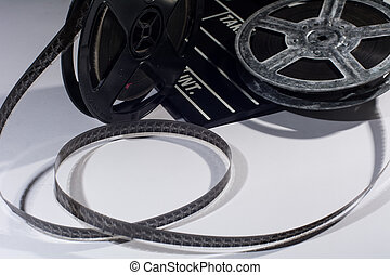Old reel of film and cinema clap lying on a light Twisted...