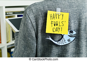 man with a note with the text happy fools day attached to...