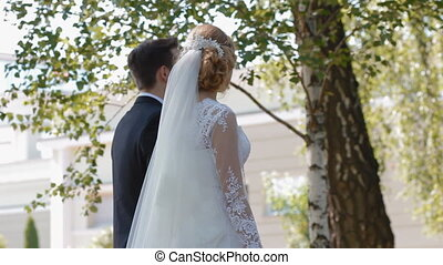Bride and groom walk in the park