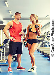 smiling man and woman talking in gym