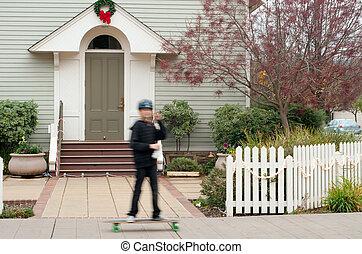 passing skateboarder in motion blur - suburban scene of a...