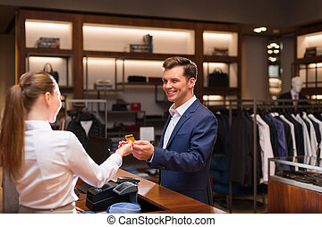 Shopping - Young businessman with seller at checkout