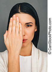 Concentrate on my look! Portrait of beautiful young woman looking at camera and covering her eye with her hand while standing against grey background