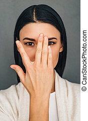 Hide and seek. Portrait of beautiful young woman looking at camera through her fingers while standing against grey background