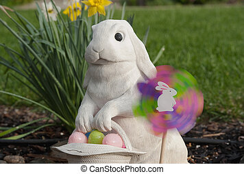 white rabbit holding an easter basket - a pinwheel spinning...