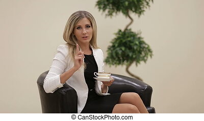 Businesswoman talking to camera with a cup of coffee -...