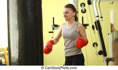 Girl in boxing pear in the gym