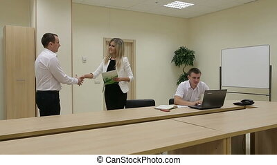 Businessman shaking hands to seal a deal with businesswoman.