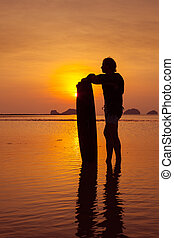 Silhouette of a man with the wakeboard on the tropical...
