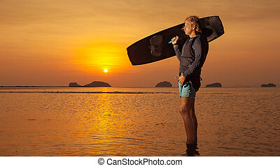 Blond man with the wakeboard on the tropical sunset...
