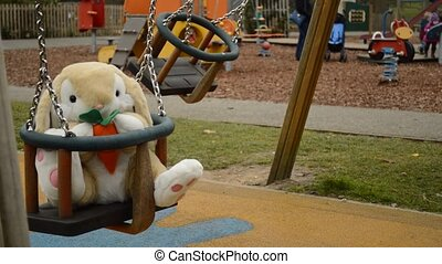 swinging soft toy bunny on the children playground. Blurred...