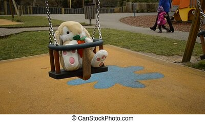 soft toy in the swing - swinging soft toy bunny on the...