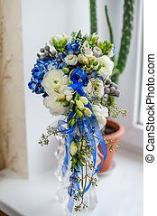 Beautiful wedding bouquet standing on the window sill in a vase